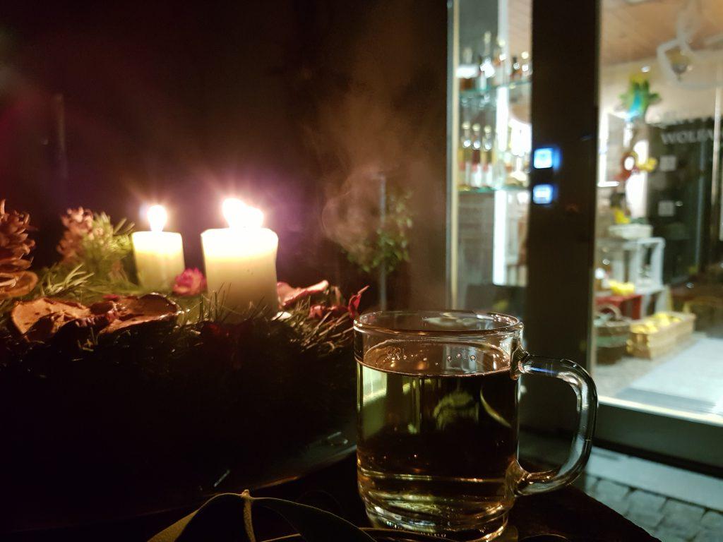 Ein Glas dampfender Quittenglühwein bei Kerzenschein des Adventskranzes vor dem Quittenladen in Astheim.